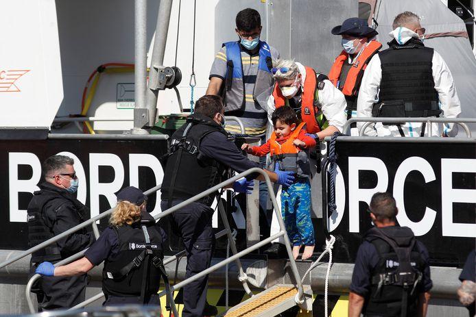 Een kind dat zojuist gered is gered door grenswacht Border Force, wordt aan wal getild in Dover.