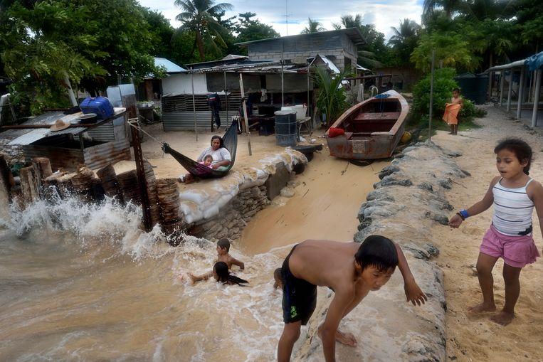 December 2012. Betio is de hoofdstad van Kiribati op het Tawara-atol. Bewoners leggen zandzakken voor de deur tegen het opkomende water. Het rif biedt geen bescherming meer.  Beeld Kadir van Lohuizen