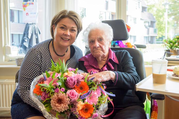 Will Linnemeyer-Calis ontvangt bloemen van burgemeester Arinda Callewaert van Bergeijk.