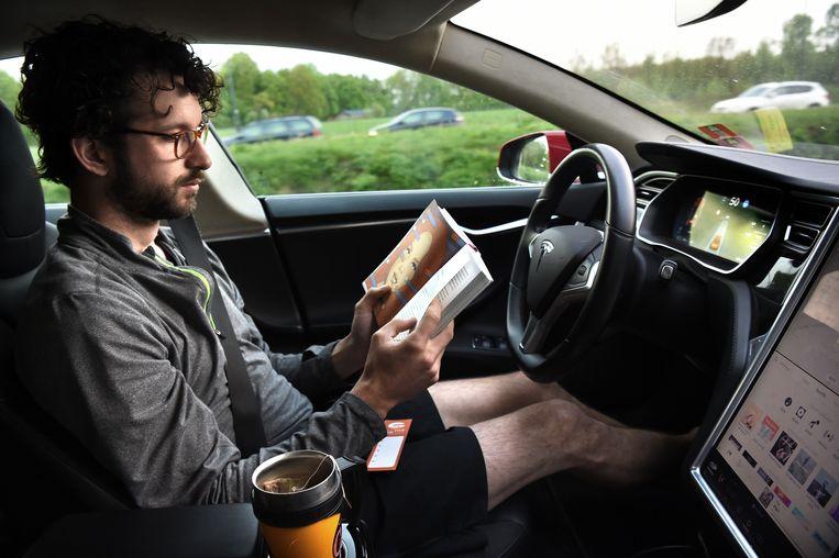 Op de autopiloot rijdt de Tesla naar kantoor. Het biedt de mogelijkheid om mailtjes weg te werken. Beeld Marcel van den Bergh / de Volkskrant