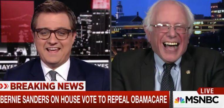 Bernie Sanders kan zijn lach niet onderdrukken tijdens een interview op de MSNBC-programma 'All in with Chris Hayes'. Beeld Screenshot MSNB