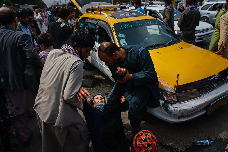 Een vrouw in Kabul wordt geholpen nadat ze gewond is geraakt in de drukte bij het vliegveld, waar mensen proberen om weg te komen. De Taliban gebruiken geweld om de menigte in bedwang te houden. Beeld Los Angeles Times via Getty