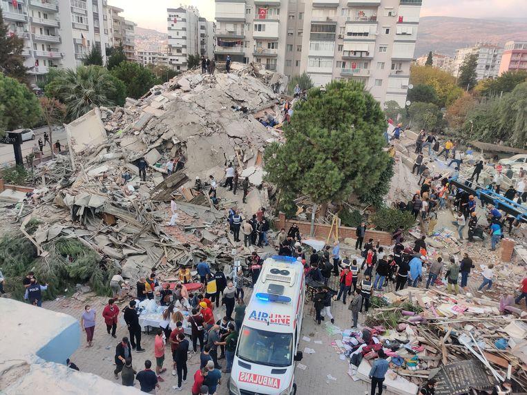 Mensen zoeken naar slachtoffers onder het puin van een ingestort gebouw in Izmir. Beeld EPA