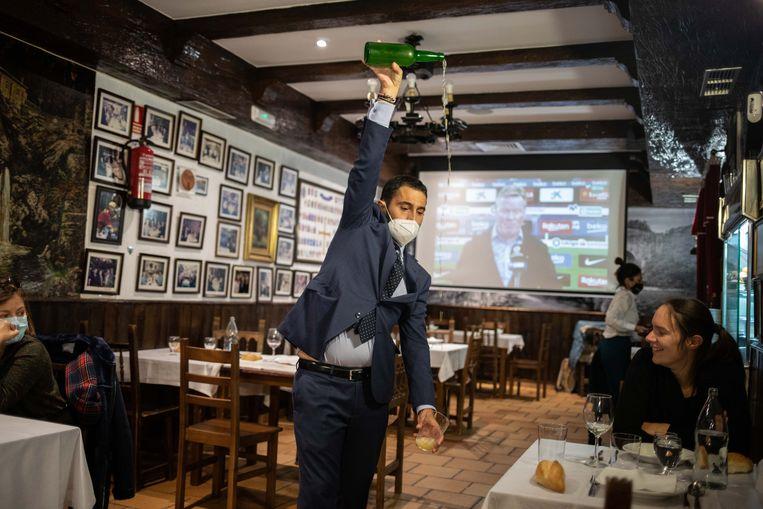 Een ober in restaurant El Ñeru schenkt een glas cider in.  Beeld Cesar Dezfuli