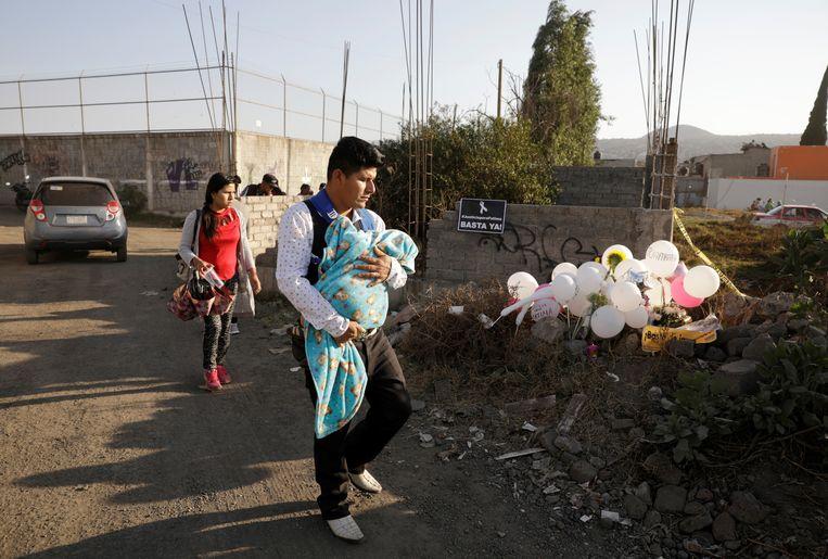 Mensen lopen langs de plek waar het lichaam van het meisje gevonden werd, op de plek waar nu ballonnen liggen. Beeld REUTERS
