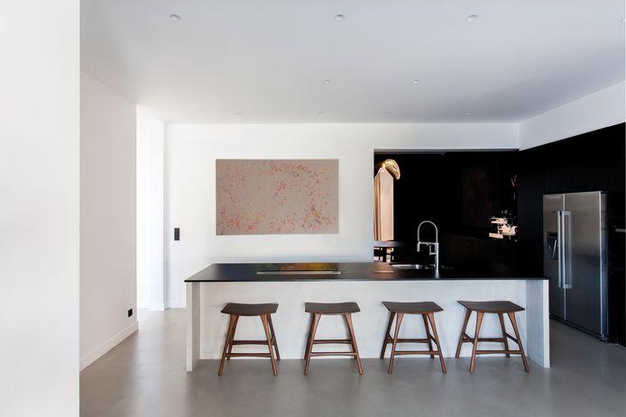 Omdat de eethoek achter dekeuken niet zo veel licht vangt, koos het koppel om hem volledig in het zwart in te richten. Enkel het plafond met sierelementen is wit.