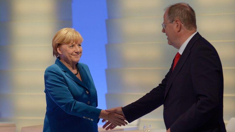 Angela Merkel schudt de hand van Peer Steinbrück, de voorman van de SPD. Beeld afp