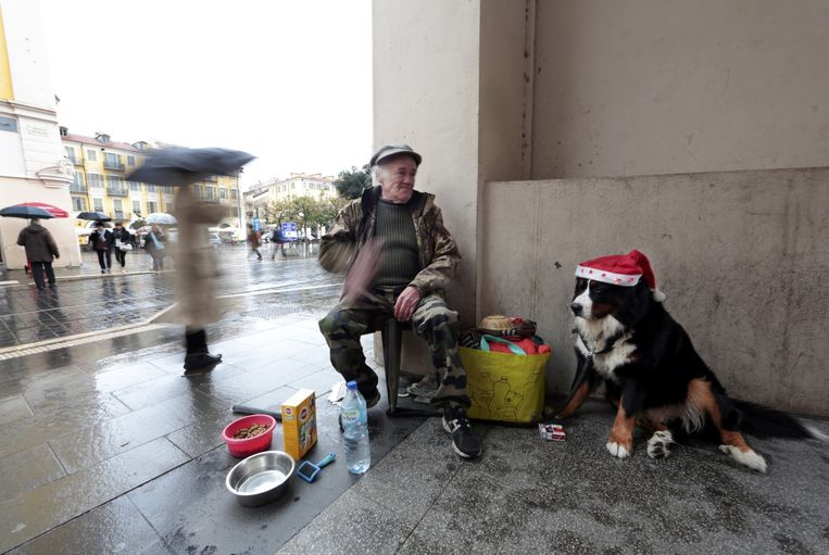 Een dakloze man met zijn hond in het centrum van Nice. Beeld REUTERS