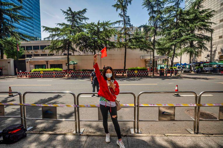 Voor de Amerikaanse ambassade in Chengdu wuift een vrouw met een Chinese vlag. Beeld EPA