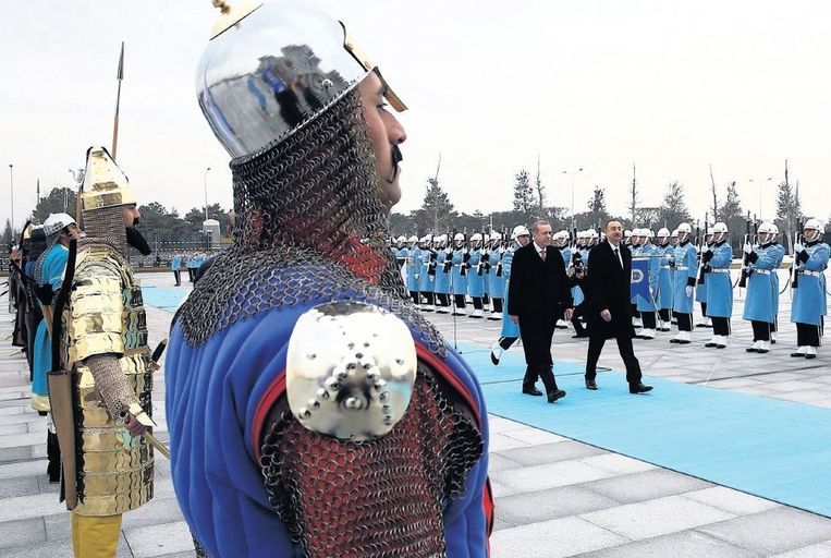 Erdogan (links in het midden) ontvangt zijn gasten met een erehaag van soldaten uitgedost in historische kostuums. De traditionele rode loper is vervangen door een blauwe variant, de nationale kleur van Turkije. Beeld epa
