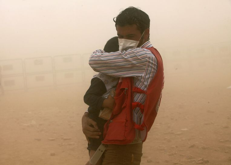 Een Turkse hulpmedewerker beschermt een Syrische vluchteling uit Kobani tegen een zandstorm Beeld ap