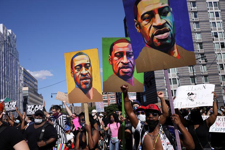 Brooklyn, New York, 13 juni. In een demonstratie tegen nodeloos politiegeweld dragen betogers borden mee met de beeltenis van George Floyd, de zwarte man die een paar weken daarvoor bij een politieactie om het leven gekomen was. Beeld REUTERS