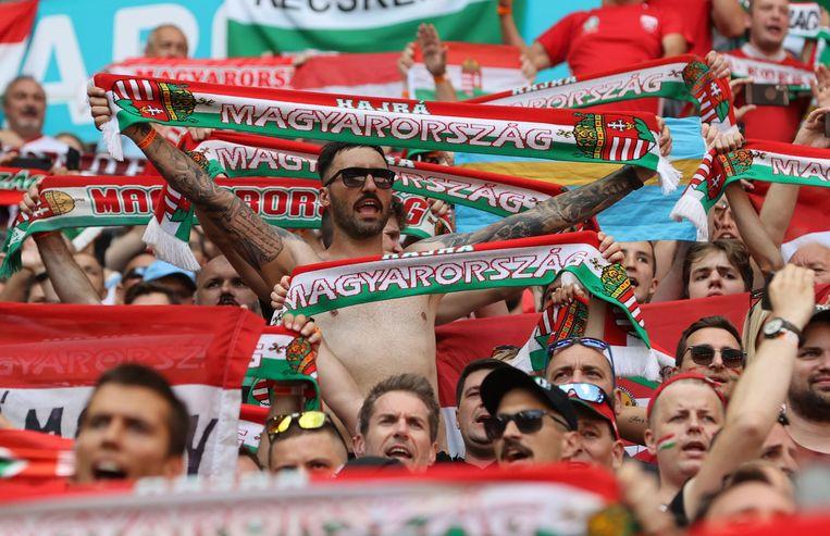 Hongaarse fans moedigen het nationaal elftal aan in Boedapest. In Hongarije gelden al langer nog amper maatregels tegen het coronavirus.  Beeld Pool via REUTERS