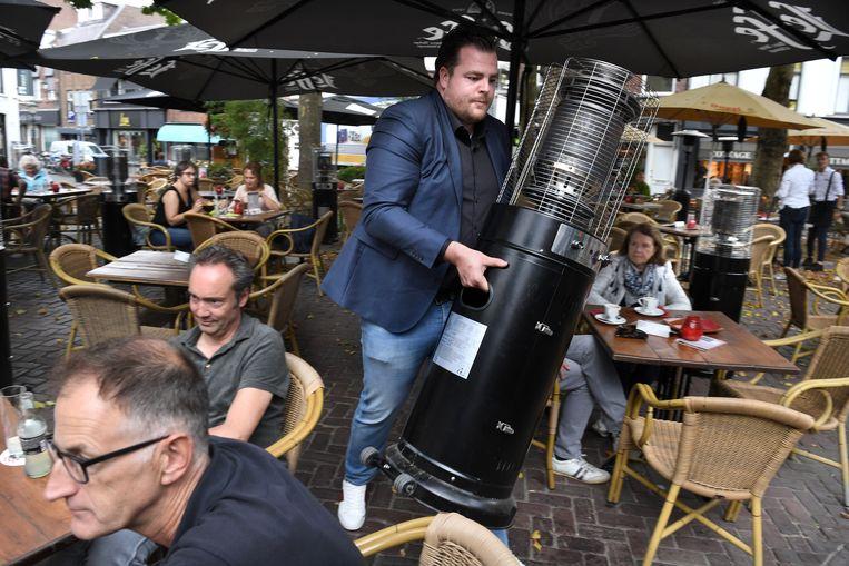 Horecaondernemer Johan de Vos van Boerke Verschuren in de weer met heaters op zijn terras in Breda. Beeld Marcel van den Bergh / de Volkskrant