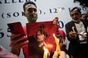 Landgenoten in Thailand steken kaarsjes aan voor de opgepakte regeringsleider Aung San Suu Kyi
