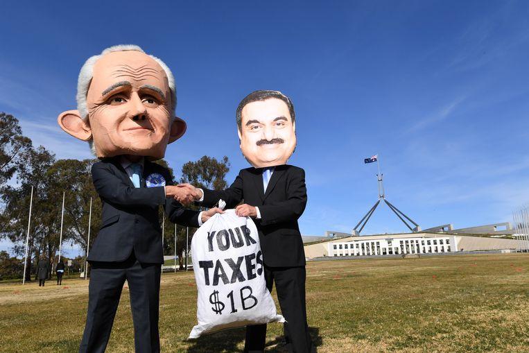 Demonstranten, in 2017, met maskers die de Australische premier Malcolm Turnbull (links) en Adani-baas Gautam Adani voorstellen. Beeld EPA