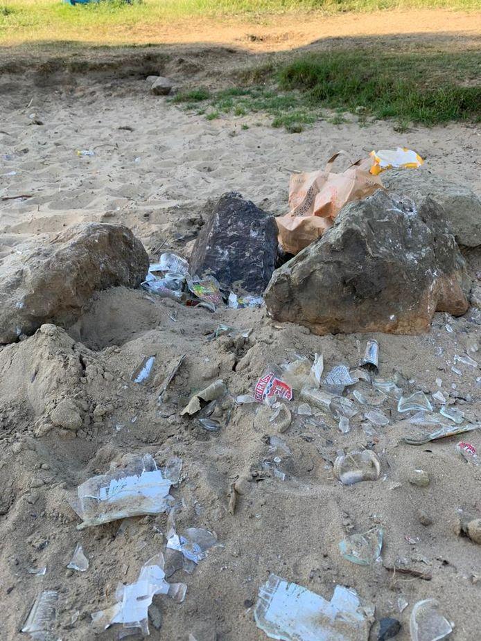 Kapotgeslagen flessen op het strandje in Lith; een Smirnoff-etiket is herkenbaar.