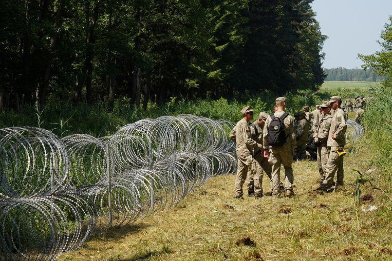 Litouwse soldaten bouwen een geïmproviseerd hek langs de grens met Wit-Rusland.  Beeld Reuters