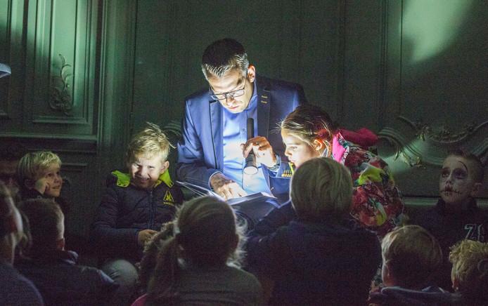 Wethouder Derk Alssema leest in een zaal van het oude stadhuis voor aan tientallen kinderen.