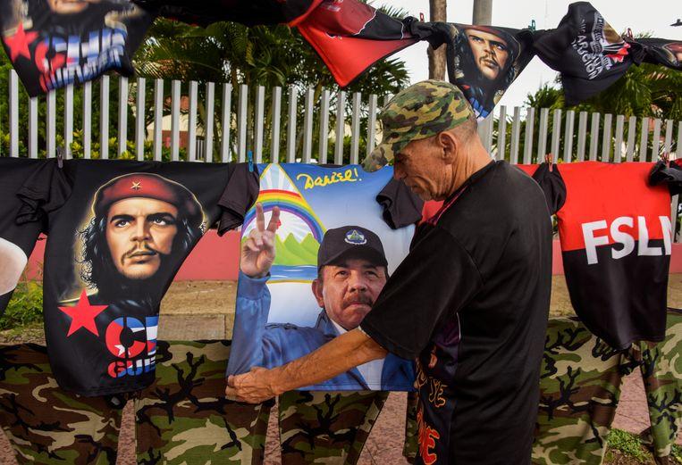 Een man hangt T-shirts op met de afbeeldingen van revolutionaire leiders, onder wie Che Guevare en Daniel Ortega, in de Nicaraguaanse stad Managua. Jagger: 'Ortega is geen revolutionaire held, maar een dief.' Beeld Getty Images