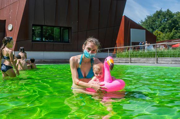 Deze vrouw neemt het zekere voor het onzekere en houdt haar mondmasker ook aan in het water.
