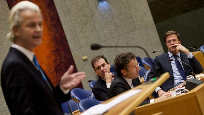 Ministers Asscher (midden) en Dijsselbloem (tweede van rechts) luisteren met premier Rutte (rechts) naar Geert Wilders tijdens het debat over het begrotingsakkoord in oktober vorig jaar.