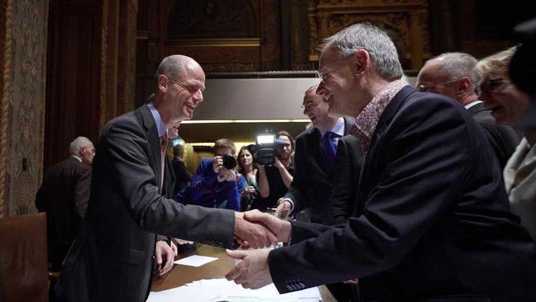 PvdA-senator Adri Duivesteijn (rechts) schudt de hand van minister van Wonen Stef Blok (VVD) na het debat over de woningmarkt in de Eerste Kamer. Beeld anp