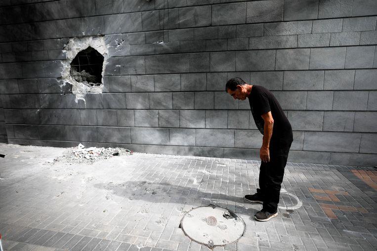 Een Israëlische man kijkt naar een raketinslag in de stad Ashkelon. Beeld REUTERS