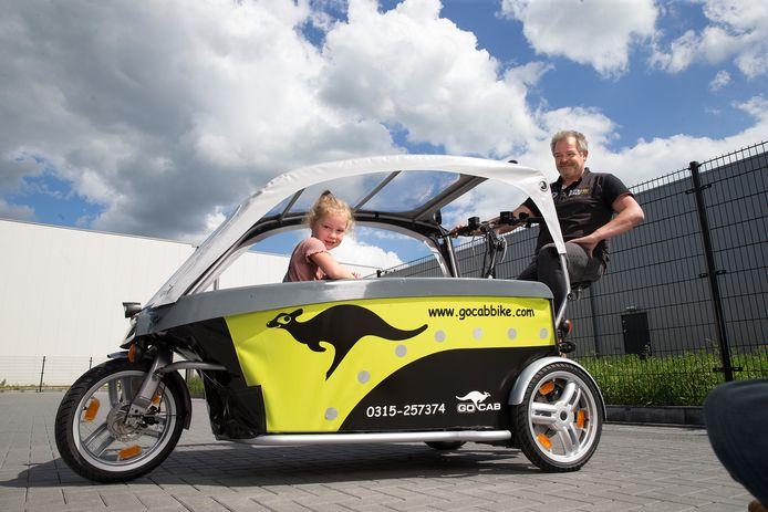 Bedrijfsleider Ariën ten Haaken op de fietstaxi voor kinderen, met Jip Vreeman, het 5-jarige dochtertje van een collega.