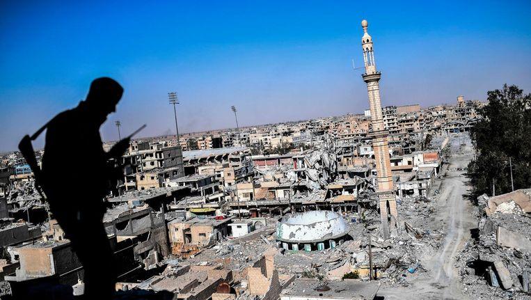 Een lid van de Syrische Democratische Strijdkrachten kijkt uit op Raqqa. Beeld afp