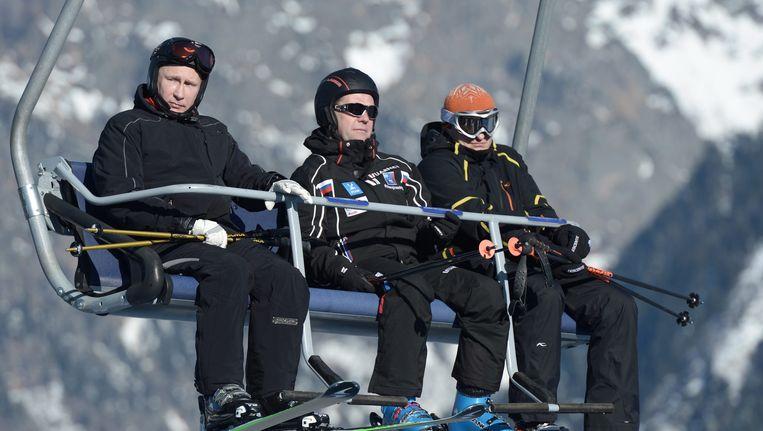 President Poetin (links) en premier Medvedev (midden) op verkenning op de skihellingen van Sotsji, begin dit jaar. Beeld EPA