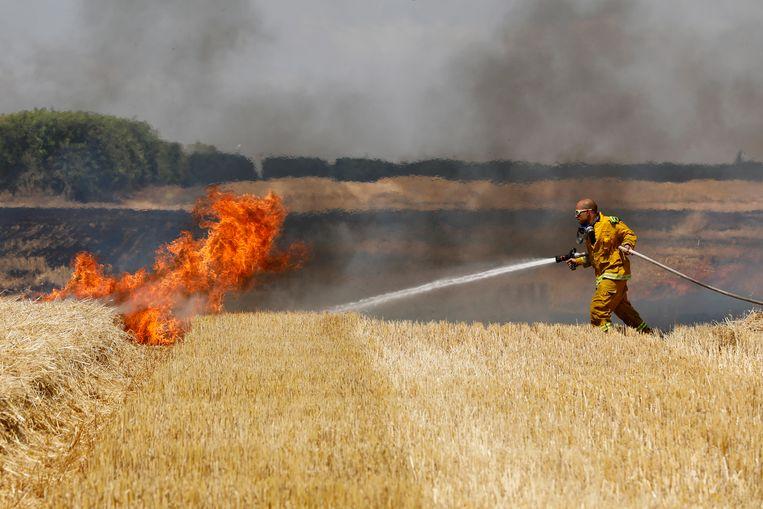 Israëlische brandweermannen proberen de branden, die door de molotovcocktails werden veroorzaakt, te blussen. Beeld EPA