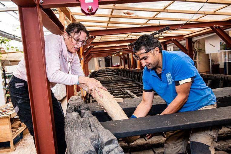 Archeoloog Yardeni Vorst en scheepstimmerman Abdulkader Shafiq werken aan de restauratie van de Romeinse Zwammerdamschepen in het Archeon.  Beeld Merel Klijzing