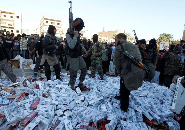 IS-strijders op bergen in beslag genomen sigaretten in Raqqa, op een foto uit 2014.  Beeld REUTERS