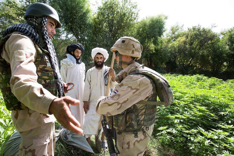 Uruzgan 2008, een Nederlandse militair en zijn Afghaanse tolk in gesprek met twee Afghaanse boeren.  Beeld Guus Dubbelman / de Volkskrant
