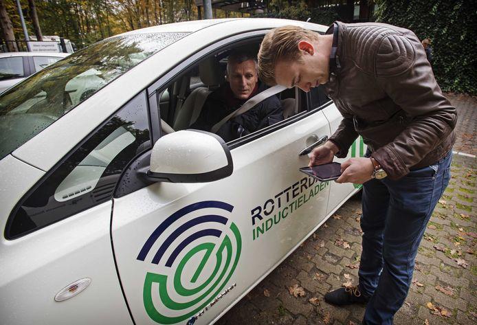 Medewerkers van de gemeente Rotterdam laden een elektrische auto op boven een laadplaat.