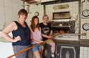 Christel Raes, dochter Ingeborg en huidig bakker Jacques Vansteenkiste bij de oven uit 1946, die nog altijd gebruikt wordt om brood te bakken.