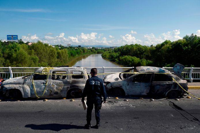 Een Mexicaanse agent bij uitgebrande voertuigen na een gewapende confrontatie tussen een drugskartel en veiligheidstroepen