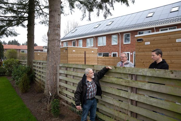 Henk van Amersfoort, Gerrit Kroes en Arno van 't Hul (vlnr) tonen aan dat je vanaf het nieuwe achterpad zo over de schutting in de tuin kan kijken. Op de achtergrond de omstreden woningen van DeltaWonen aan de Spoorlaan.