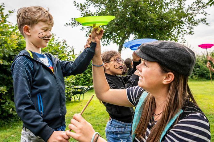 Tussen de fruitbomen van Bierbrouwerij Oijen leren kinderen verschillende circustrucs. Hier oefent Rico (l) met de borden, geholpen door Yrsa Snepvangers van Circus Snor.