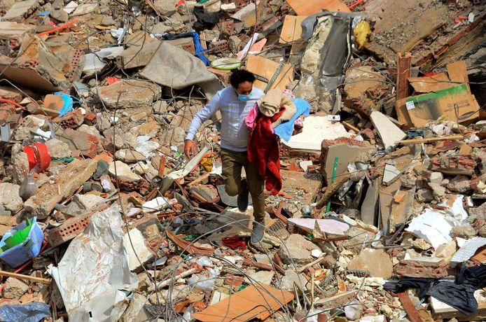 Een man probeert spullen terug te vinden in de puinhopen van het ingestorte gebouw.