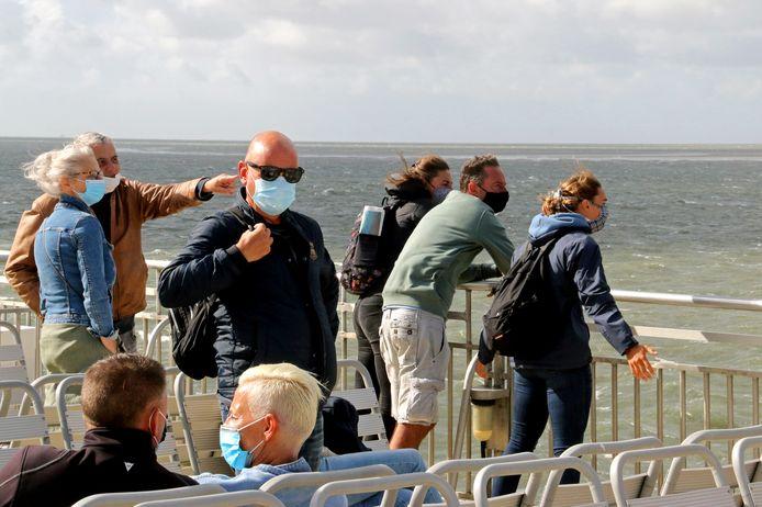 Passagiers met de verplichte mondkapjes op het bovendek van de veerboot van Harlingen naar Vlieland.