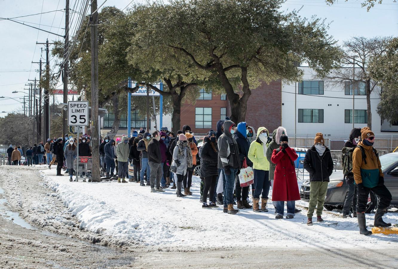 Mensen staan buiten in de kou in de rij om boodschappen te gaan doen.