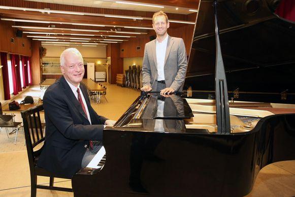 Olivier De Spiegeleir achter de piano in de gemeentelijke feestzaal, samen met schepen van Cultuur Steve Roobaert (LVB-Drogenbos Plus).