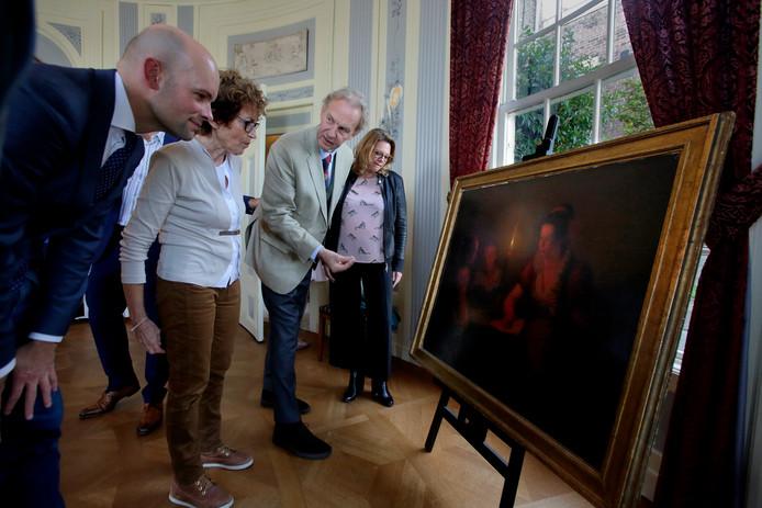 Jaap Versteegh (links) overhandigt het kaarslichtschilderij van Michiel Versteegh aan bestuurslid Johan de Haan en conservator Hélène Bremer.