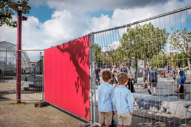 Op het stuk Museumplein in Amsterdam waar normaal een vijver is, wordt hard gewerkt aan het podium en het toeschouwersgedeelte van de Uitmarkt plaats zullen gaan nemen. Beeld Patrick Post