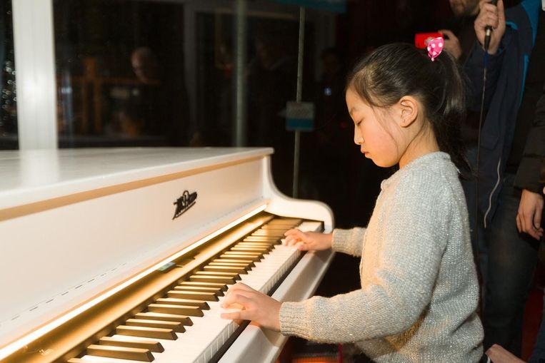 De tienjarige pianovirtuoos Zhang Wang Yelin bedient een installatie door op het instrument te spelen.