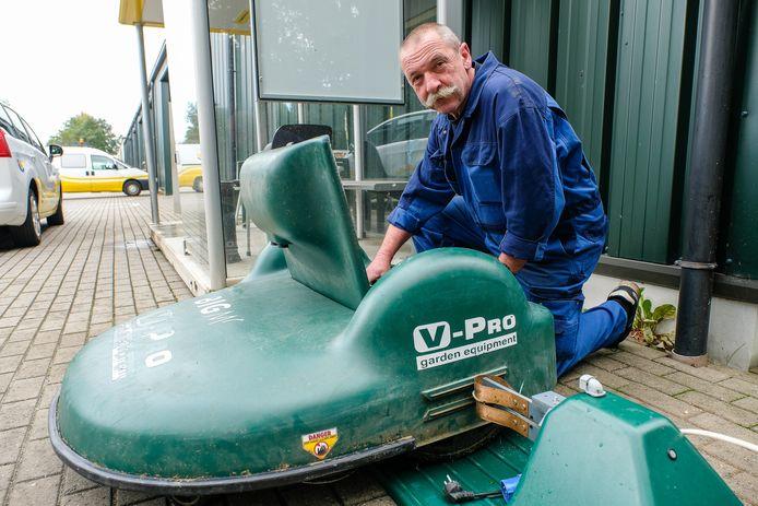 Eddy Van Lommel controleert de machine. De kap waaronder de messen zitten, moet hersteld worden.