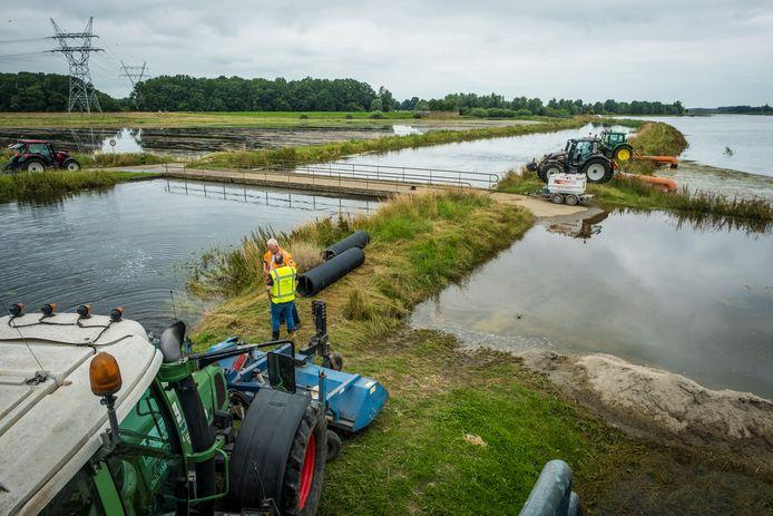 Drie grote machines pompen de uiterwaarden bij gemaal Hoenwaard bij Hattem leeg, na de dijkdoorbraak in juli.
