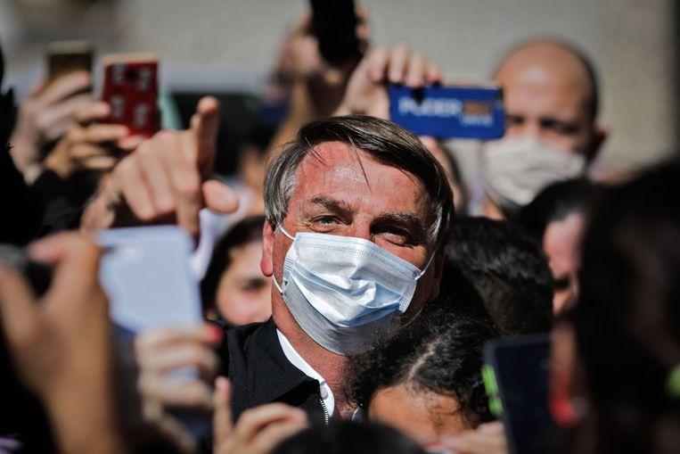 President Jair Bolsonaro wordt omringd door supporters en reporters in de hoofdstad Brasilia. Beeld AFP